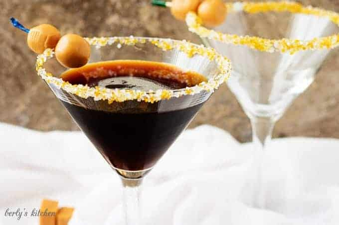 "Salted Caramel Coffee Martini with ""caramel olives"" in a long-stemmed martini glass."