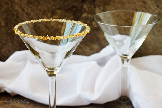 Two empty martini glasses, one rimmed with gold and white sugar.