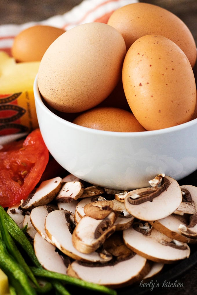 A white bowl filled with brown eggs. The bowl is surrounded by the sliced veggies.
