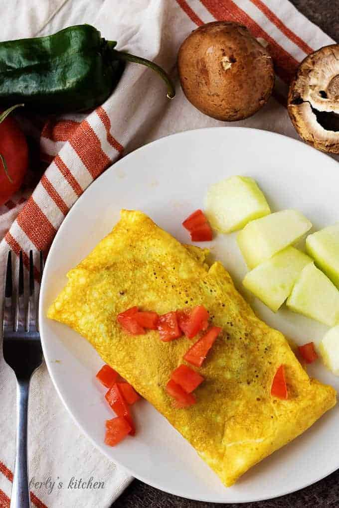 A top-down view of the dish with the omelet and melon chunks. Omelet is garnished with diced tomato.
