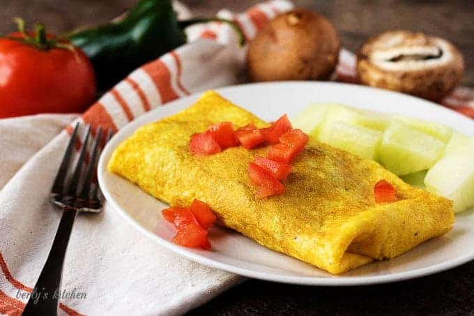 A white plate with the omelet. It's topped with tomatoes and served with melon chunks.