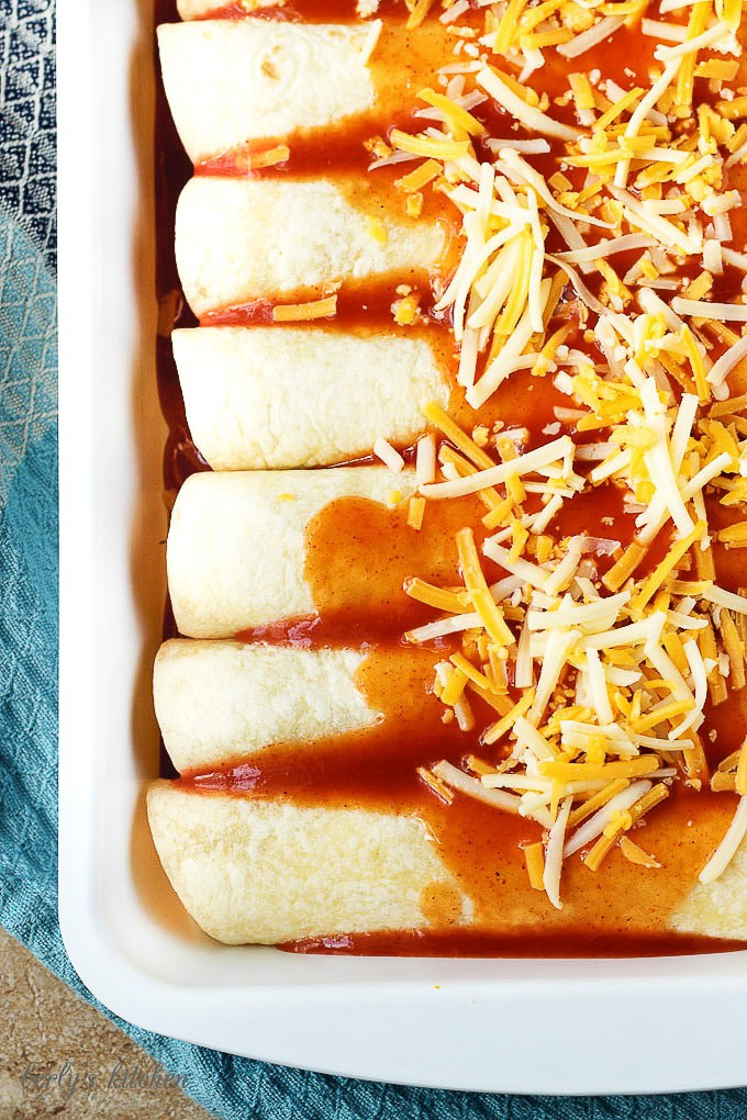 The prepped enchiladas smothered with sauce and shredded cheese blend.