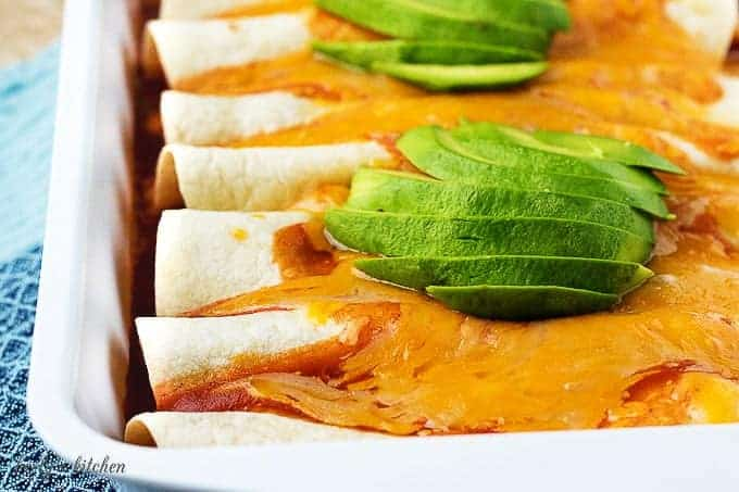 The cooked chorizo enchiladas covered in cheddar cheese, sauce, and sliced avocado.
