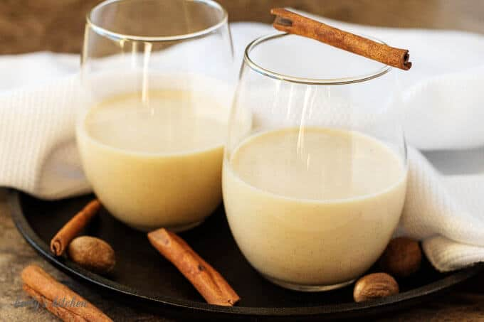Two small glasses half-filled with coquito garnished with cinnamon and nutmeg.