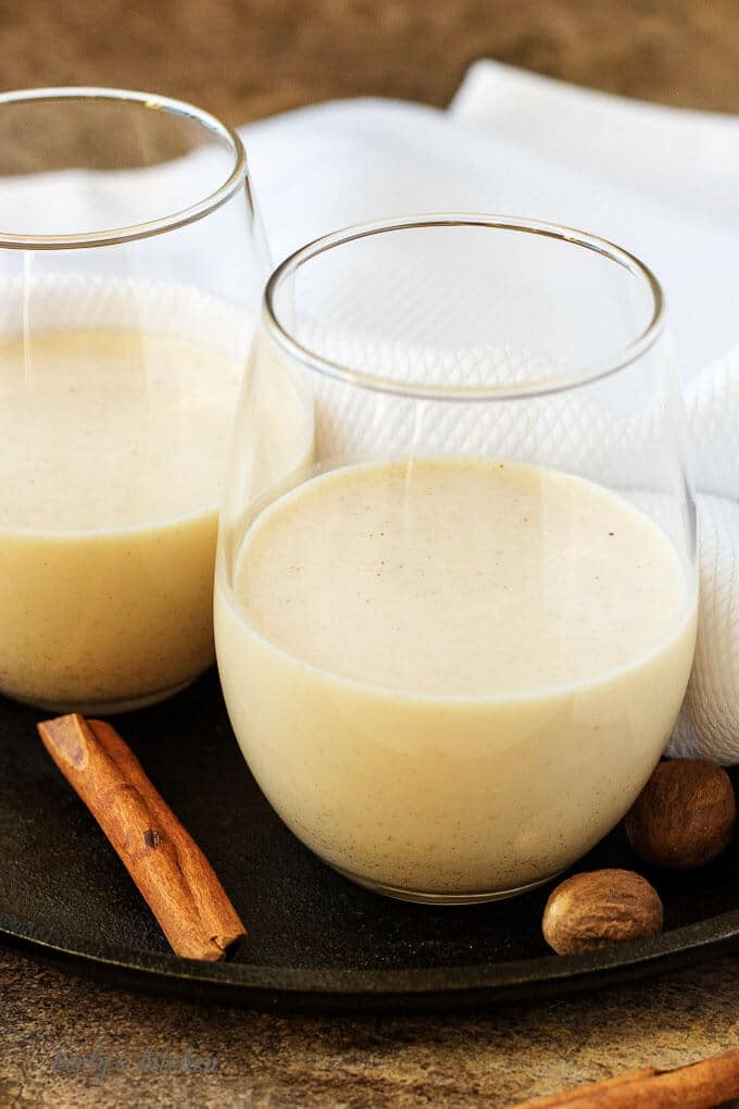 Two glasses half filled with coquito, chilled and ready to serve with cinnamon.