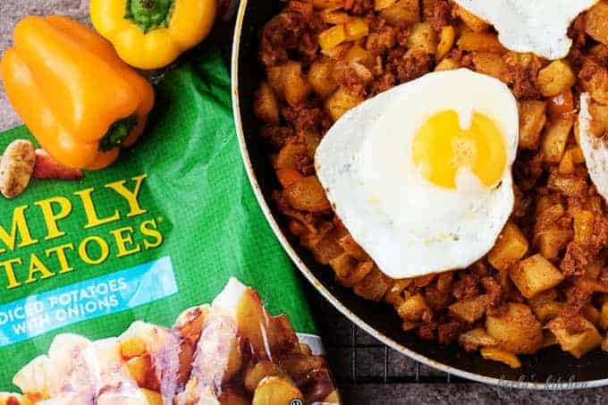 Chorizo hash topped with sunny-side up eggs in a non-stick skillet. Orange sweet peppers and the Simply Potatoes bag are in the picture.