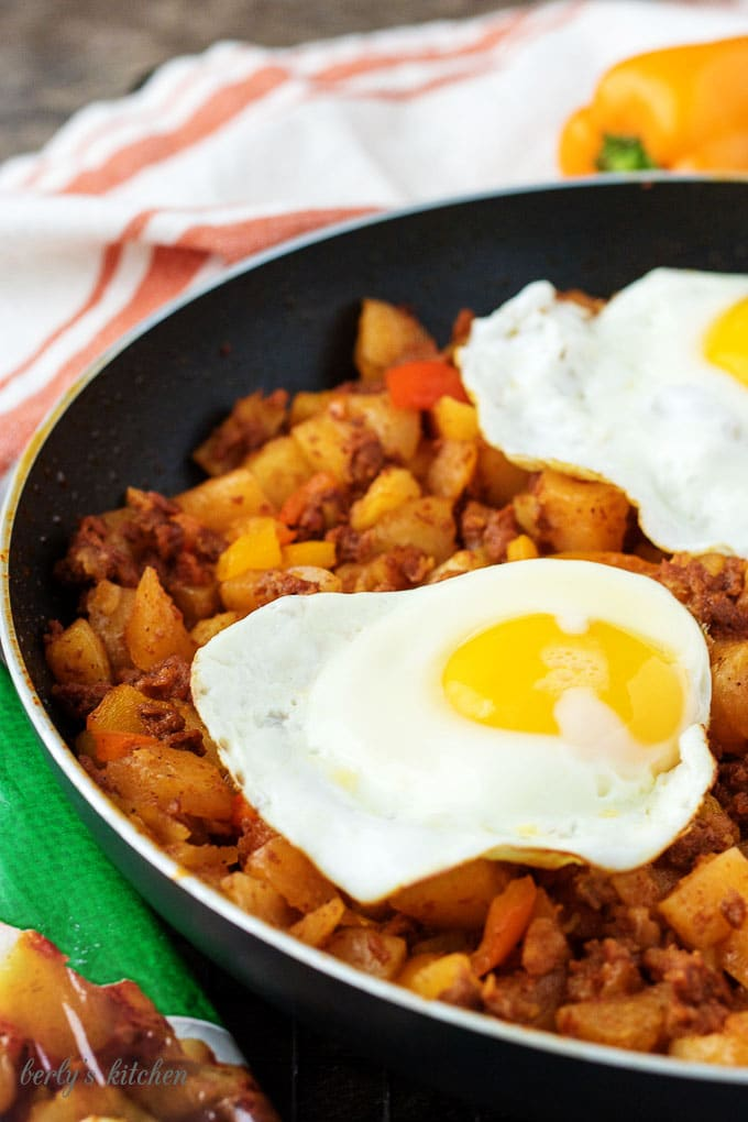 The finished has in a black non-stick skillet topped with two sunny-side up eggs.