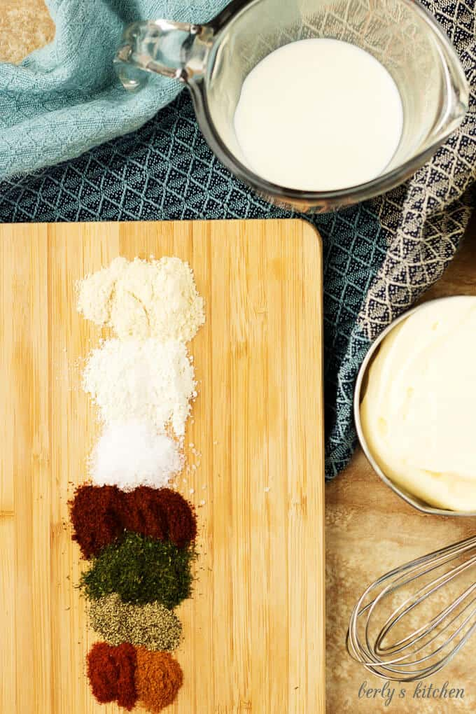 Buttermilk and whole milk are set next to spices like dill and garlic powder.