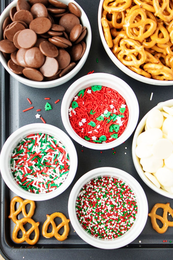 Top-down view of the ingredients, white and dark melting chocolate, mini-pretzels, and colorful sprinkles.
