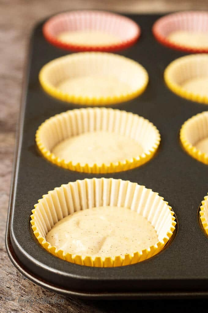 A side-view of the colorful cupcake liners in a cupcake pan half-filled with batter.
