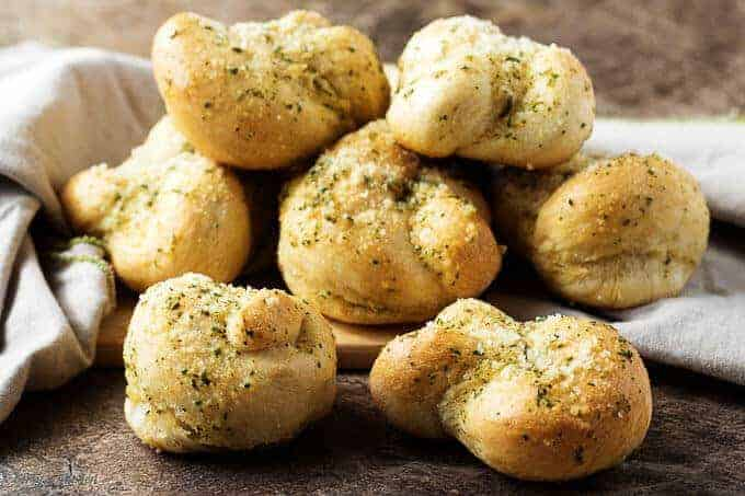 The finished garlic knots recipe showing the garlic butter topped knots stacked on cutting board.