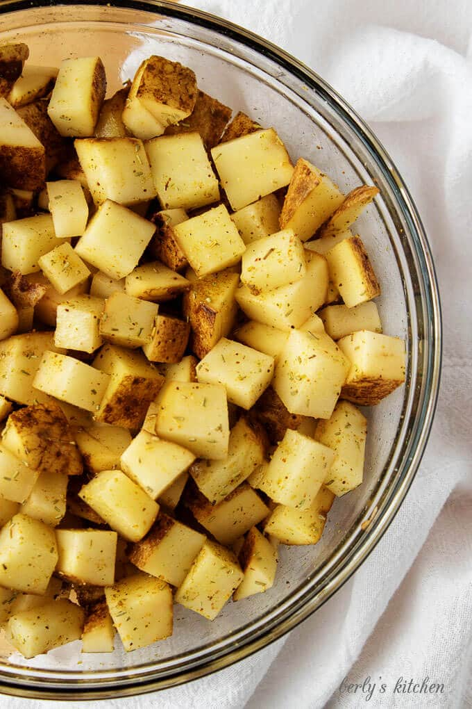 Top-down view of the potatoes, tossed with olive oil and seasonings.