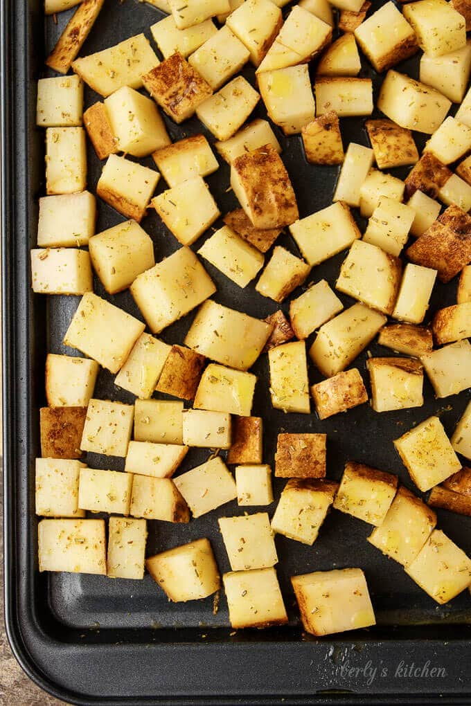 The home fries have been spread out evenly on a dark sheet pan for baking.