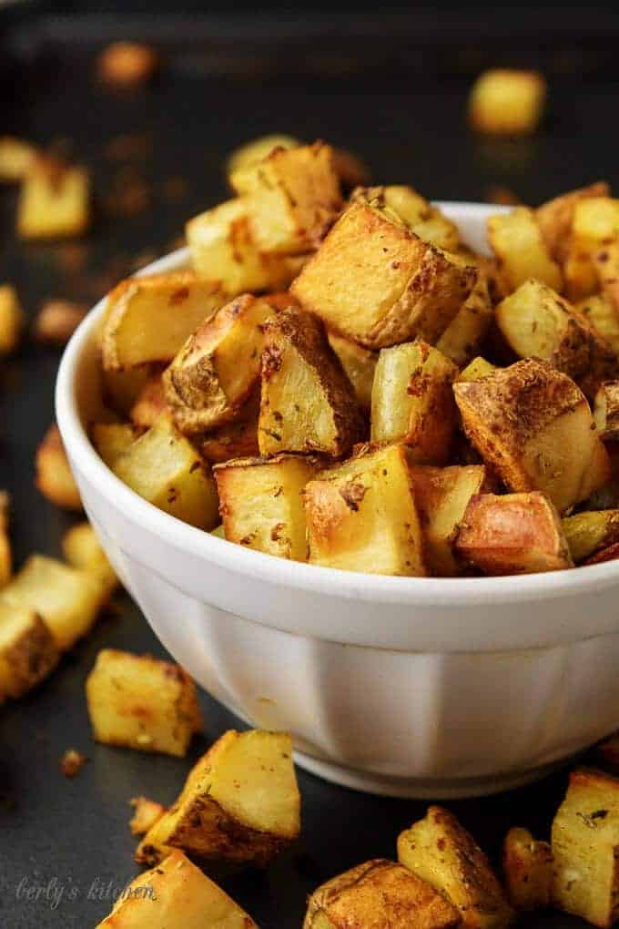 Oven-baked home fries in a white bowl on a sheet pan.