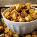 The finished home fries recipe showing the crispy fries in a bowl sitting on a pan.