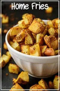 A close-up picture of the finished home fries recipes in a white bowl on a dark sheet pan.