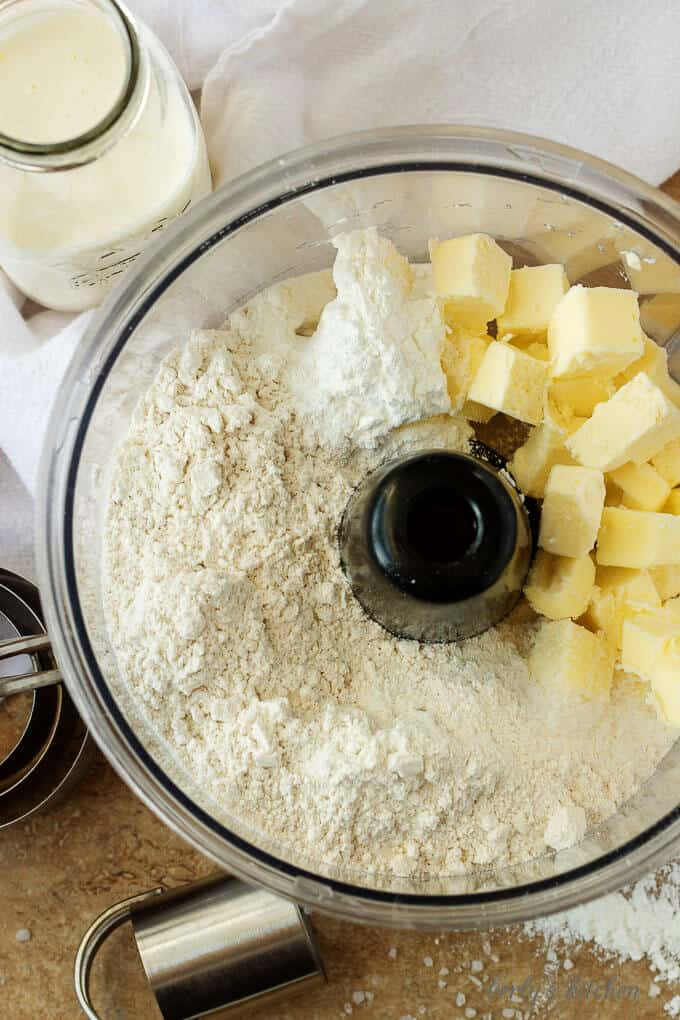 Flour, baking powder, salt, and butter needed for homemade buttermilk biscuits in a food processor.