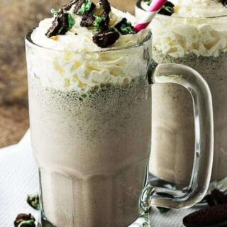 Two Oreo milkshakes in chilled mugs with whipped cream and cookies toppings .