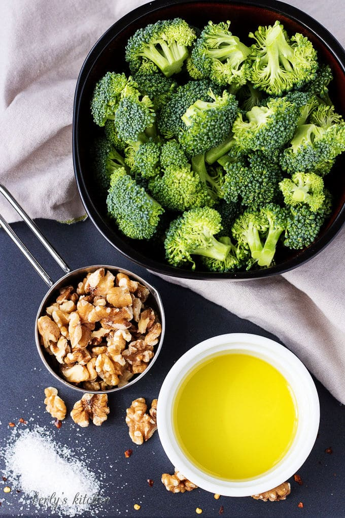 A top-down view of the ingredients like broccoli, olive oil, walnuts and spices.