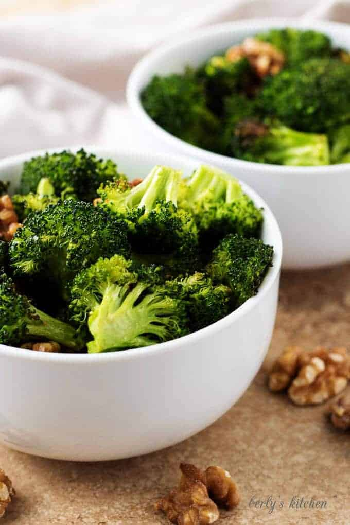 A close-up picture of the finished oven roasted broccoli separated into two serving bowls.