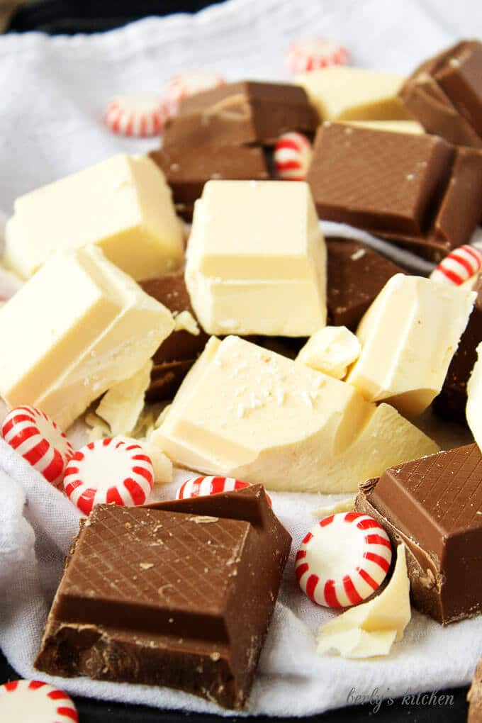 Top-down view of the ingredients, squares of milk and white chocolate and peppermint candies together.