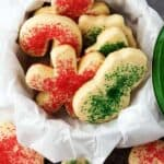 The sugar sprinkled cookies, cut into holiday shapes like trees and snowmen, in a cookie tin.