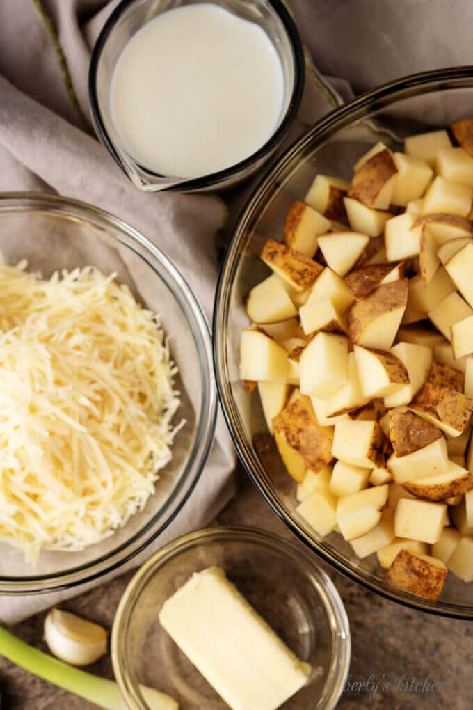 An aerial photo of the ingredients like diced potatoes, butter, and shredded Parmesan cheese.