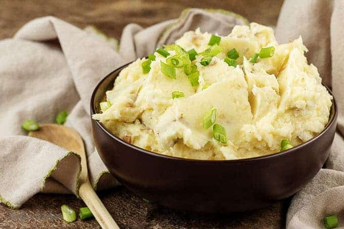 The finished Parmesan mashed potatoes in a serving bowl garnished with diced green onions.