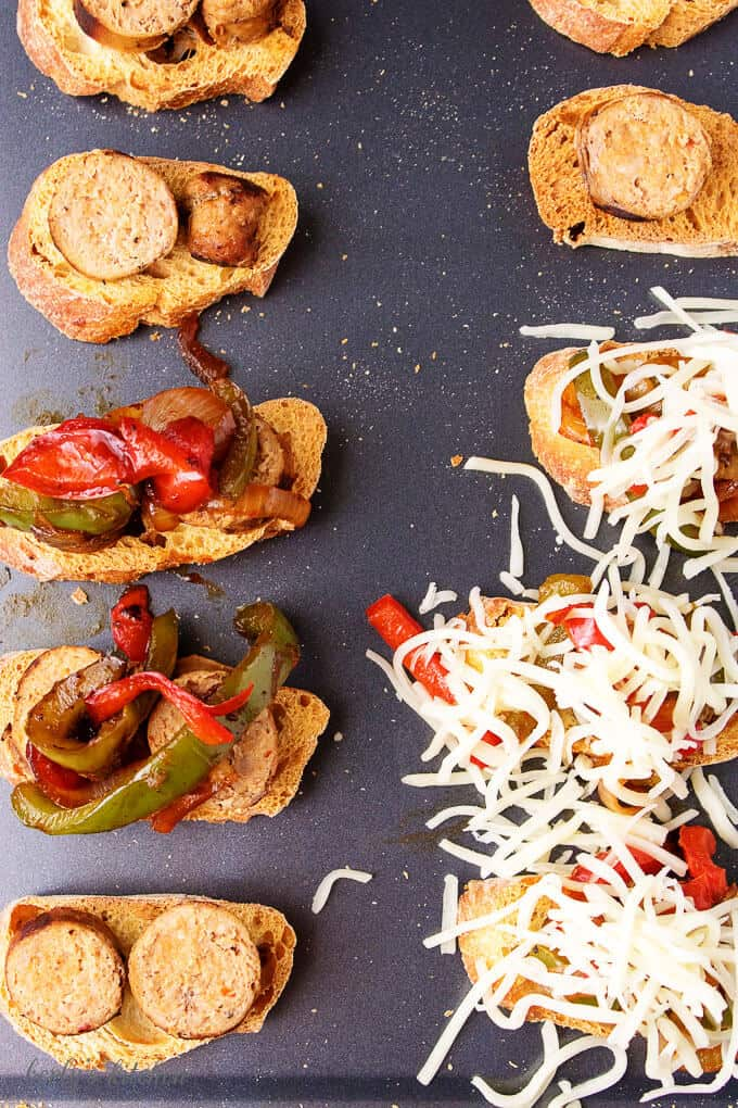 The sausage and peppers crostini bites on a sheet pan being topped with mozzarella to bake.