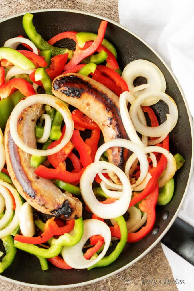 Top-down shot of the sausage and peppers cooking in large saute pan.