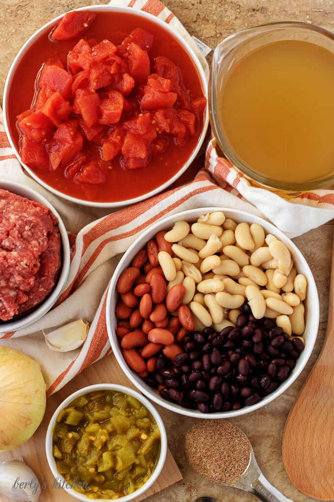 An aerial photo of the ingredients like, ground beef, beans, diced tomatoes, and garlic.