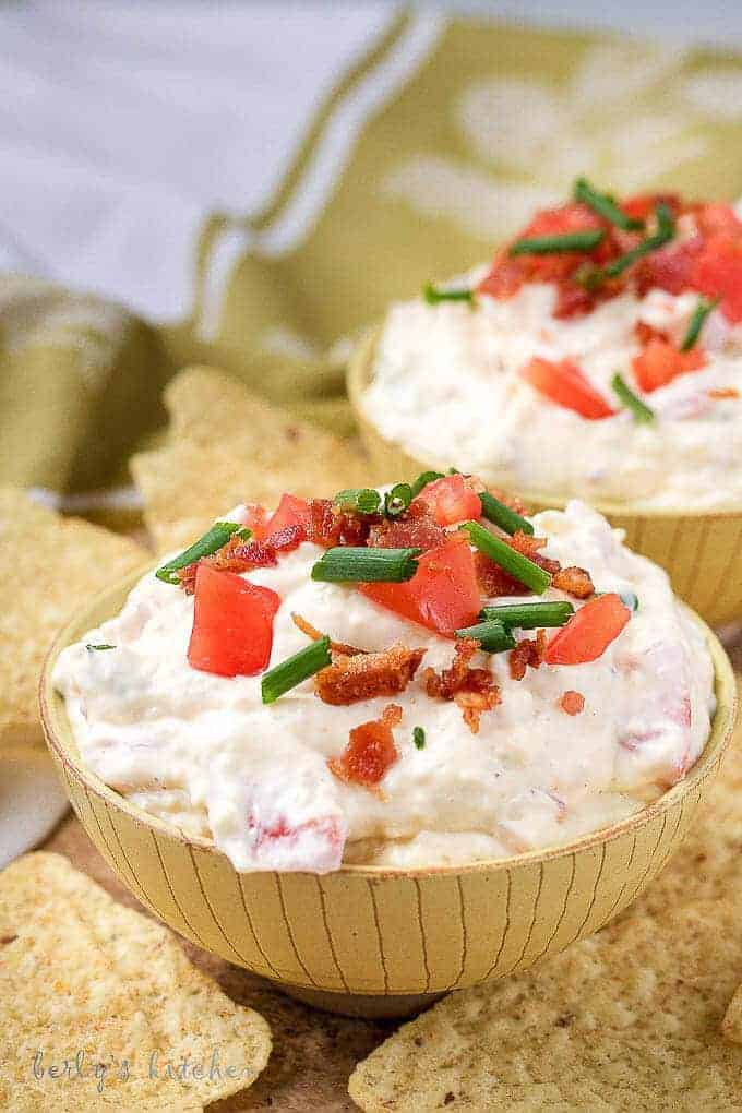 A close-up picture of the finished blt dip in yellow bowls, served with tortilla chips.