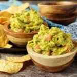 Chipotle guacamole in wooden bowls with tortilla chips.