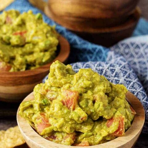 Close up of chipotle guacamole in wooden bowls sitting on a blue towel.