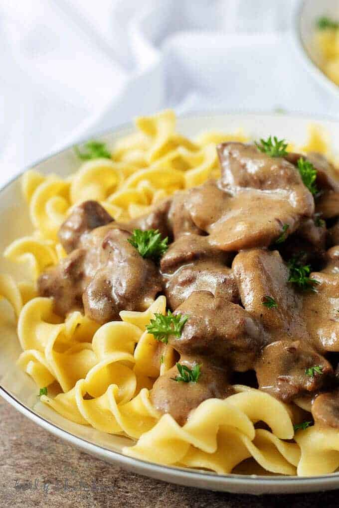 Close up of beef stroganoff on a white plate with a white napkin in the background.