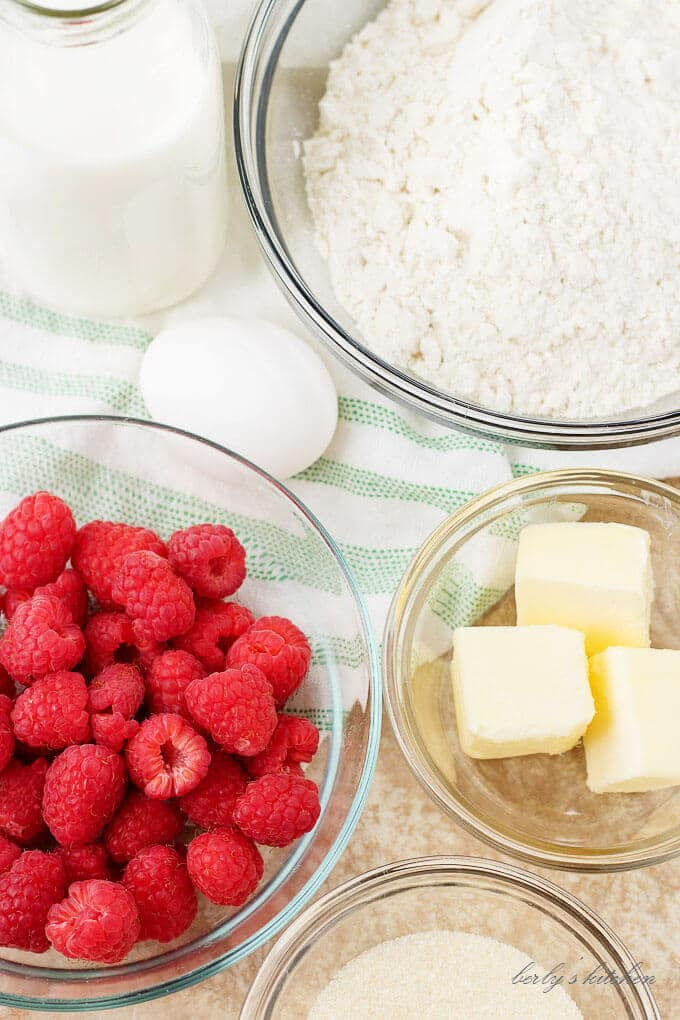 An aerial view of the ingredients, like butter, raspberries, and flour mix.