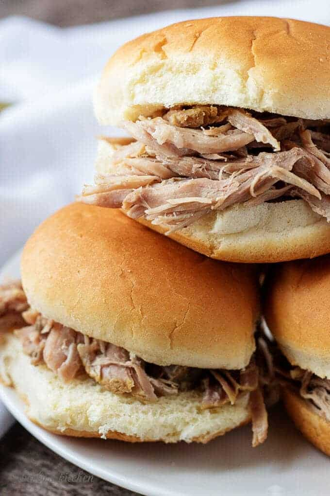 Pork pot roast sandwich stacked on a white plate.