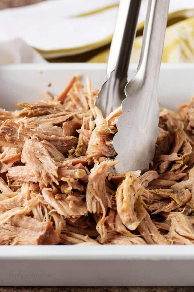 Shredded pieces of pork pot roast in a pan with tongs.