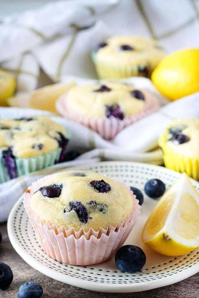 Finished lemon blueberry muffins on a small plate garnished with blueberries and a lemon wedge.