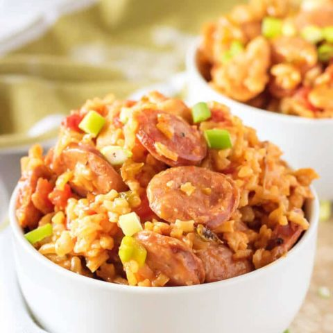 Close up view of sausage and chicken jambalaya in two white bowls with scattered green onions.
