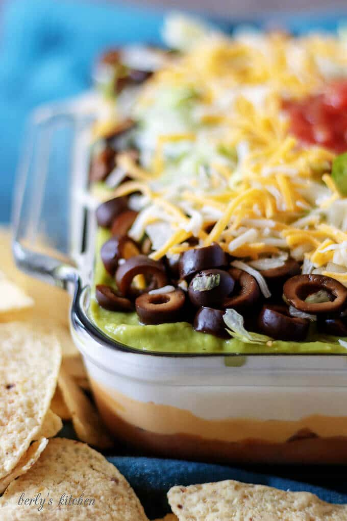 A close-up view of the 7 layer dip in which all the layers can be seen in the clear glass baking dish.