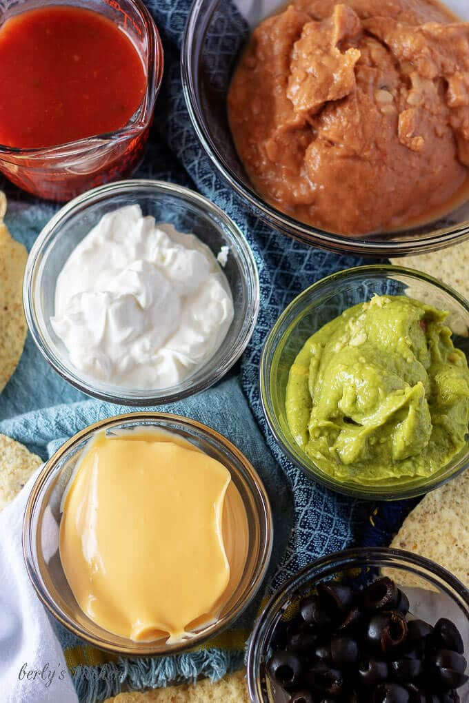 An aerial photo of the 7 layer dip ingredients like, guacamole, sour cream, and nacho cheese sauce.