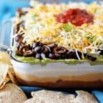 The finished 7 layer dip topped with salsa, in a large casserole dish on a blue towel.