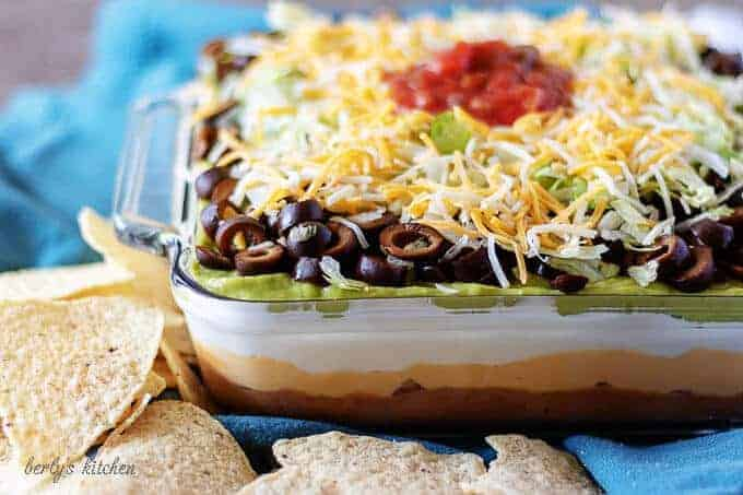 7 layer dip topped with salsa, in a large casserole dish on a blue towel.