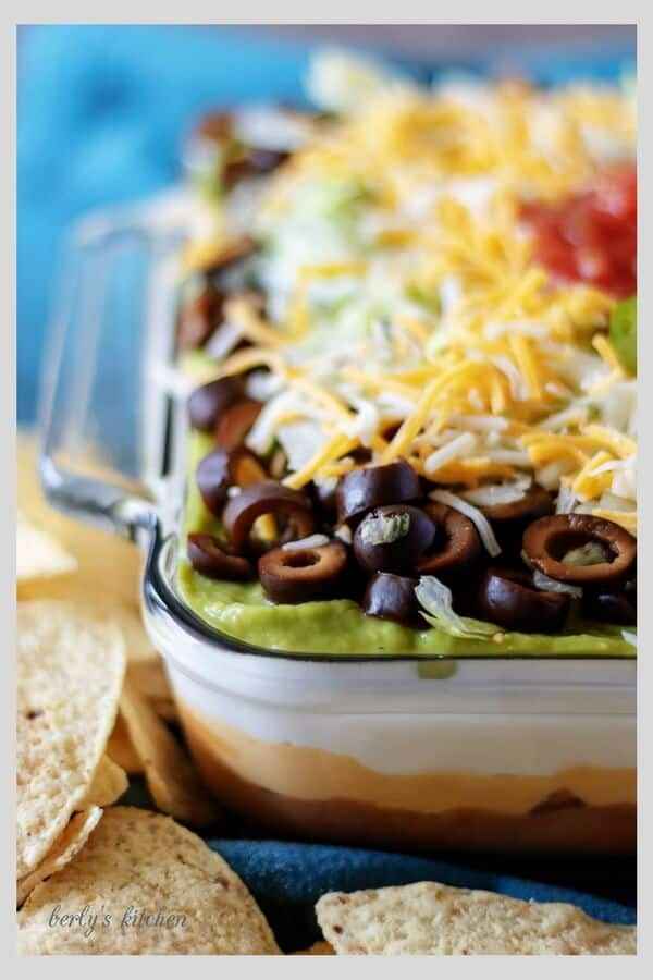 A close-up photo of the finished 7 layer dip loaded with cheese, olives, and sour cream.