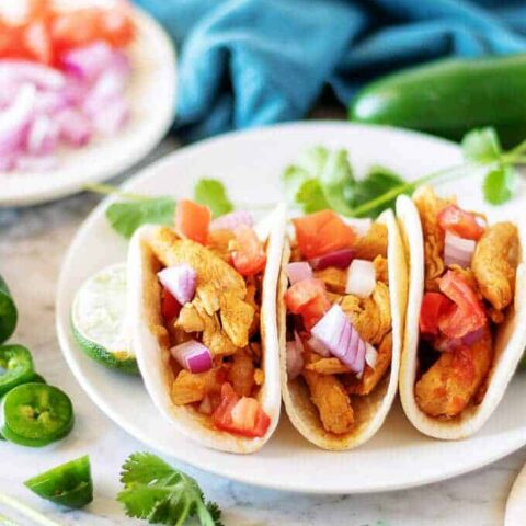 A close-up picture of the finished chicken soft tacos garnished with toppings likes cilantro, red onion, and diced tomatoes.