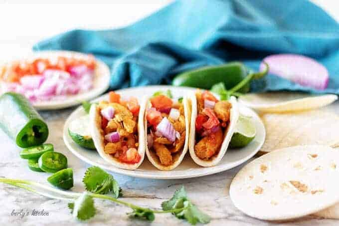 Three finished instant pot chicken soft tacos on a white plate garnished with red onions and tomatoes.