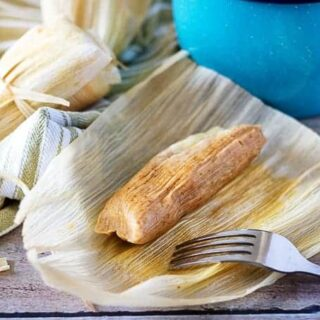 Homemade tamale in an open corn husk next to two tamales and a blue bucket.