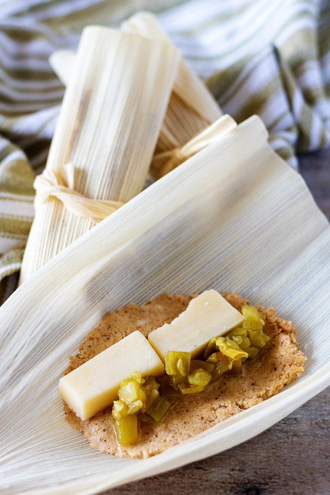 Open corn husk with masa filling, cheese, and green chiles next to closed tamales.