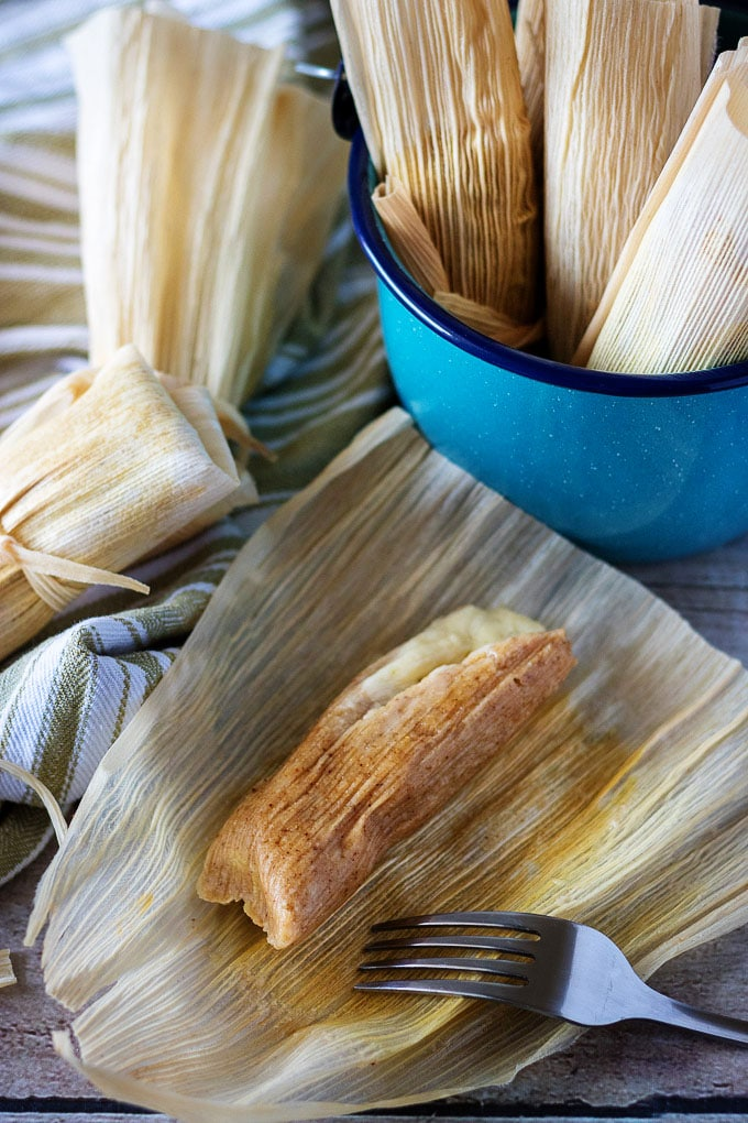 Open tamale in a corn husk next to more tamales in a blue bucket.